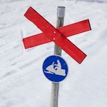 The blue sign means that it's not permitted to drive snowmobiles outside the trail. The red cross means that this is also a ski trail. Snowmobiles must give way.